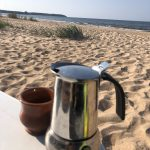 Espressokanne und Keramiktasse am Strand