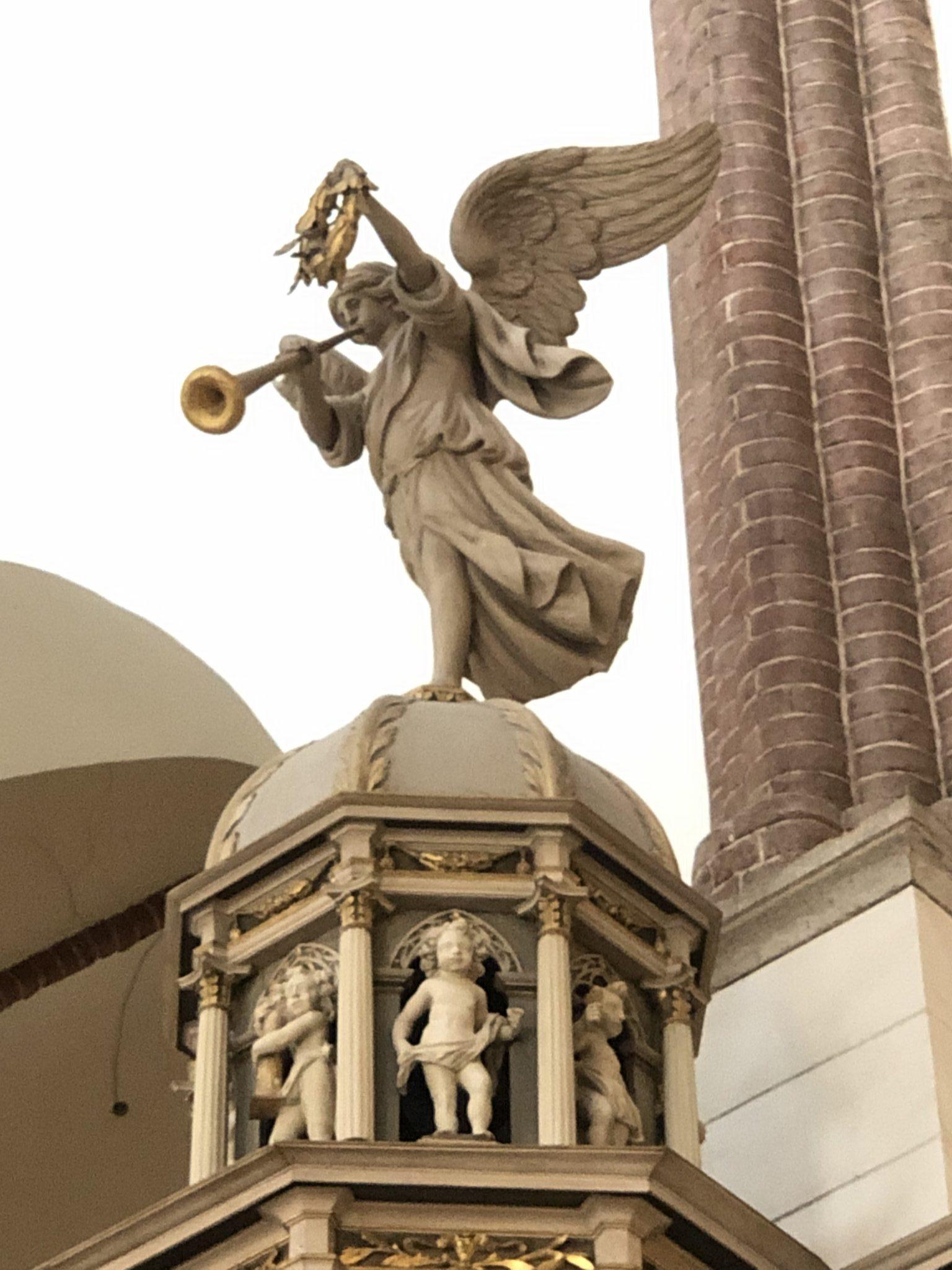 Ein Engel posaunt den Frieden von den Dächern von Riga