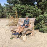 Normen entspannt auf einer Holzbank auf der Kurischen Nehrung