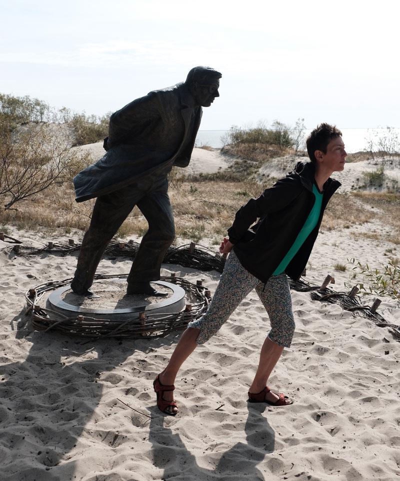 Skulptur aus Bronze und eine Persone lehnen sich gegen den Wind